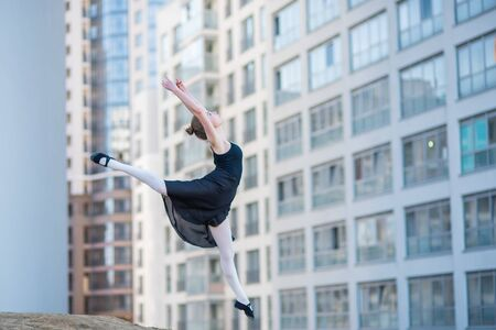 Ballerina in tutu posing against a residential building. Beautiful young woman in black dress and pointe shoes jumping with incredible flexibility. Ballerina performs elegant jumping with deflection.