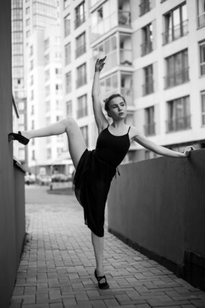 Ballerina in tutu makes an elegant pose. Beautiful young woman in black dress and pointe dancing over city background. Portrait of a gorgeous ballerina performing a dance outdoors. Black and white Фото со стока