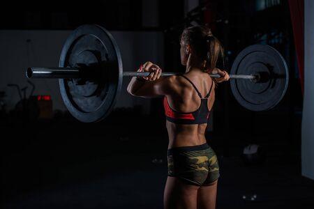 Mujer fitness joven muscular europea en pantalones cortos de color caqui haciendo ejercicio de peso muerto pesado en el gimnasio crossfit
