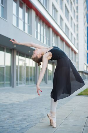 Ballerina in a tutu posing in front of a multi-storey residential building. Beautiful young woman in black dress and pointe shoes with incredible flexibility. Gorgeous ballerina performs an elegant backbeat