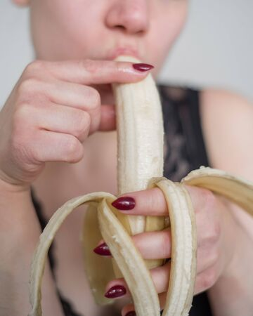 Close-up of the face, lips, tongue of a young, European girl licking a big yellow, sweet banana.