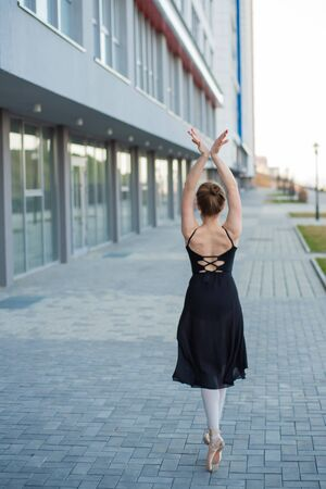 Ballerina in a tutu posing against the backdrop of a residential building. Beautiful young woman in black dress and pointe shoes dancing ballet outside. Фото со стока