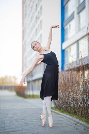 Ballerina in a tutu posing against the backdrop of a residential building. Beautiful young woman in black dress and pointe shoes dancing ballet outside. Elegant classical dance