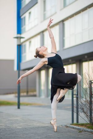 Ballerina in a tutu posing against the backdrop of a residential building. Beautiful young woman in black dress and pointe shoes dancing ballet outside. 写真素材