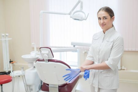 Attractive female doctor in white uniform puts on gloves. Young beautiful female dentist brunette in the office by the chair wearing gloves.