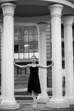 Ballerina in a tutu and pointe shoes makes a beautiful pose. Black and white photo.A beautiful young woman in a black dress is dancing in pointe classics against the background of columns.
