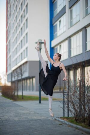 Ballerina in a tutu posing against the backdrop of a residential building. A beautiful young woman in a black dress and pointe shoes demonstrates an excellent stretch. Ballerina is standing in the spl 写真素材
