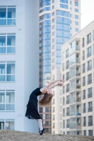 Ballerina in a tutu posing at a multi-storey residential building. Beautiful young woman in black dress and pointe shoes with incredible flexibility. Gorgeous ballerina performs an elegant backbeat.