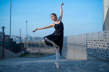 Ballerina in a tutu posing next to the fence. Beautiful young woman in black dress and pointe dancing over city background. Portrait of a gorgeous ballerina performing a dance outdoors