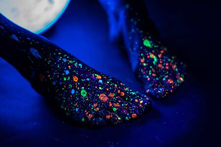 Barefoot female feet in a spray of paint glowing in the dark. Toes in fluorescent powder. Body art glowing in ultraviolet light, like a blue night sky with stars. Close up.