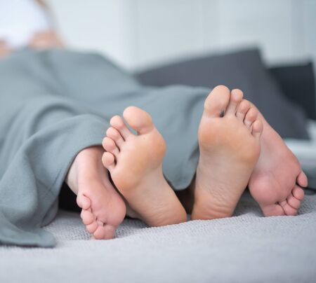 Close-up of male and female legs. The loving couple lies and embraces on the bed under a gray blanket. Light room. Imagens