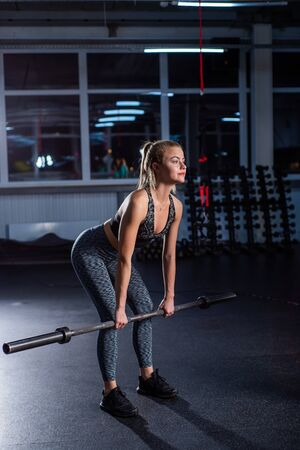 Young sports girl does deadlift with a barbell in the gym under the supervision of a trainer. Female trainer teaches ward deadlift. Personal training. Exercises on the buttocks.