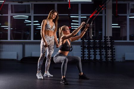 A woman does squats with TPX loops in a personal training with a trainer in the dark gym. Functional training. The coach helps the athlete to do the exercises correctly on the buttocks.