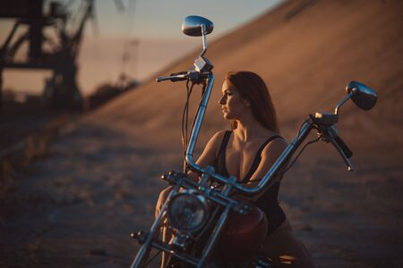 Red-haired woman in sexy lingerie in high heels sits on a motorcycle. Attractive red-haired girl sits on a motorcycle at sunset Banque d'images - 131315693