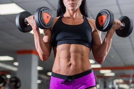 Una chica poderosa, fuerte y musculosa con hermosos músculos abdominales sostiene pesas en sus manos. Luz del día y ABC Foto de archivo