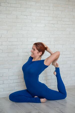 Red-haired woman in a blue jumpsuit practices yoga in a bright room. Sibit girl in dove pose, bending back