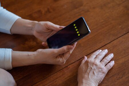 Two women vote in a smartphone while sitting at the table. Hands of mother and daughter holding a phone and arrange the rating. Experience . Close-up phone Stock fotó
