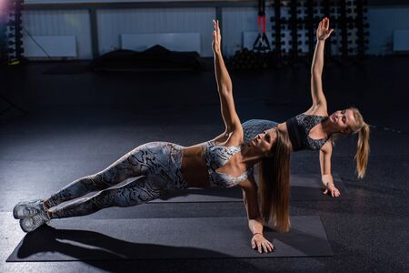 Two beautiful women with athletic figures perform a side bar in a dark gym. Two female athletes make balance from yoga.