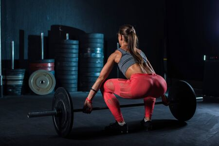 Young, European, muscular girl in red leggings, doing exercise with a barbell in the gym for crossfit. Dark background