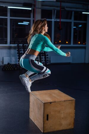 Fit young woman doing box jumping on dark background with copy space. High jump on one foot on a box. Beautiful athlete performs a circular workout. Squatting .