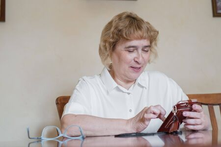Beautiful elderly woman in a white blouse sitting at the table and writes messages in the phone. Retired woman scored points and reads the message in the smartphone Stock Photo