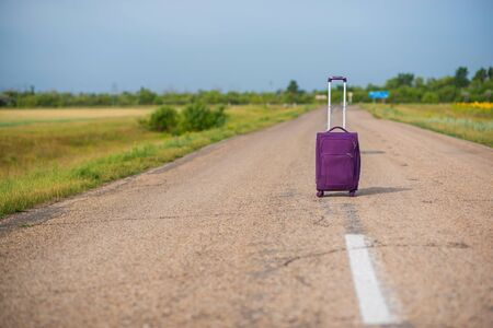 Purple suitcase on wheels with a raised handle stands in the middle of an empty asphalt road in the fields. Summer, Sunny weather, travel.
