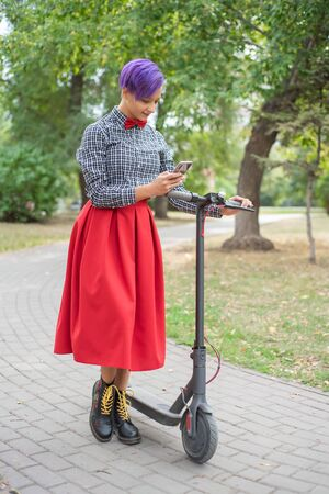 A young woman with purple hair is riding an electric scooter in the park. Stylish girl with a shaven temple in a checkered shirt, a long red skirt and bow-tie writes a message on a smartphone. Hipster Stok Fotoğraf