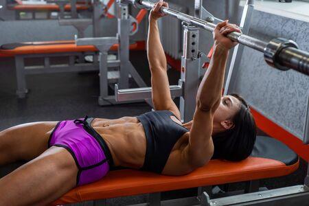 Powerful, strong, muscular girl in short shorts, performs bench press. Daylight. 版權商用圖片