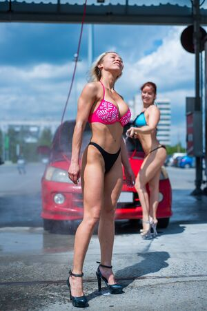 Luxury girls in seductive bikinis wash a car in a street car wash and water each other. Blonde and red-haired with beautiful figures wash a red car at a manual car wash. Self-care, dry cleaning salon. Stock Photo