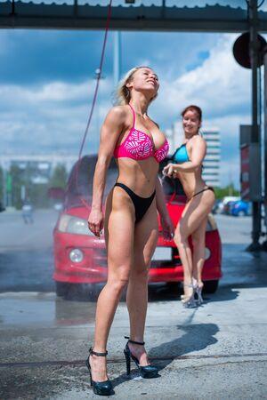 Luxusmädchen in verführerischen Bikinis waschen ein Auto in einer Straßenwaschanlage und tränken sich gegenseitig. Blond und rothaarig mit schönen Figuren waschen ein rotes Auto in einer manuellen Waschanlage. Selbstpfleger, chemischer Reinigungssalon. Standard-Bild