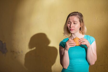 Portrait of a cute girl in a green dress walking outdoors and eating a burger on a warm summer day. Beautiful blonde is enjoying fast food at the yellow wall outside. Wrong food habits.