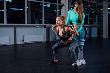 Young athletic girl doing barbell squats in the gym under the supervision of a trainer. A female coach teaches a ward to squat with a bar. Personal training. Exercises on the buttocks. 版權商用圖片