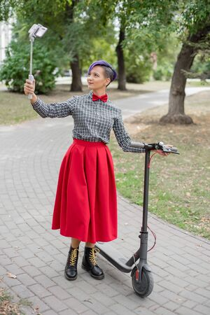 A young woman with purple hair rides an electric scooter in a park. Stylish girl with a shaved temple in a plaid shirt, a long red skirt and a bow tie takes a photo using a selfie stick. Hipster.