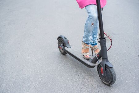 Close-up of female legs in ripped jeans and high-heeled sandals next to an electric scooter. A girl in a pink jacket quickly moves around the city on a convenient electric transport.