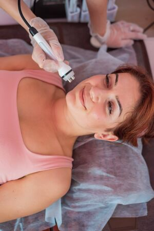 Young redhead woman gets an electric facial massage in the fight against aging. 30 year old woman receives electric ultrasonic facial massage against wrinkles in a beauty salon. Hardware cosmetology.