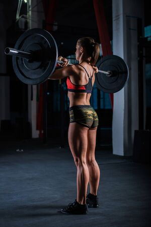 European muscular young fitness woman in khaki shorts doing heavy deadlift exercise in crossfit gym 版權商用圖片