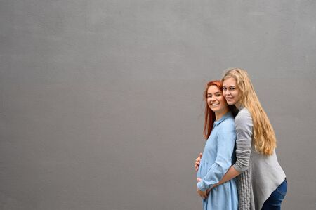 Same-sex relationships. A red-haired pregnant woman in a denim dress is standing against a gray wall, her hand is resting under her tummy. Her wife gently hugged the expectant mother from behind. Standard-Bild