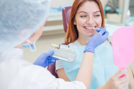 Check and select the color of the teeth in the dentists chair. Dentist makes the process of treating a beautiful young redhaired girl. Selection of a dental implant. Patient looking in the mirror.