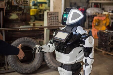 Humanoid robot on wheels with a monitor on his chest, shaking hands with a man. The old cluttered garage.