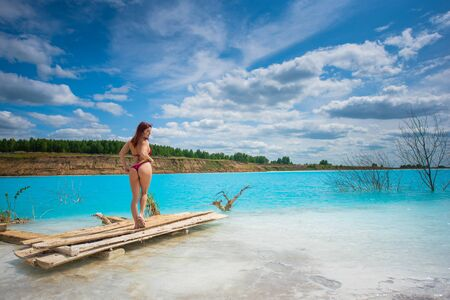 A beautiful red-haired woman in a seductive crimson bikini is standing by an unusual turquoise lake. A miracle of nature, bright blue clear water. The girl at the poisoned lake. Ash dump.