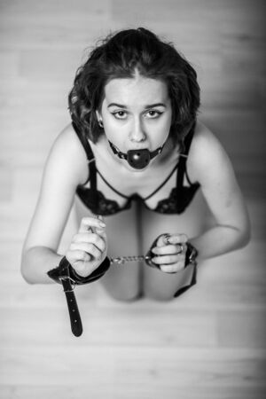 Slavery in society. The girl is on her knees with a gag in her mouth. Sexual toy. Woman slavery. Slave attire for playing games. Frightened slave. Black leather with gag. Scared hostage