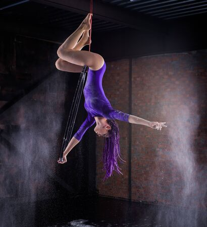 A young, slender girl in a lavender leotard and lilac dreads, doing gymnastics on the air ring, the Hoop and throws the hands of the white powder in the form of a cloud.