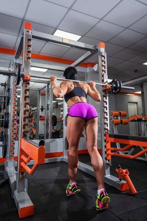 Athletic brunette doing barbell squats in the gym. Beautiful woman getting ready for bodybuilding competition. The girl is losing weight by the summer, preparing a figure for the bikini season. 版權商用圖片