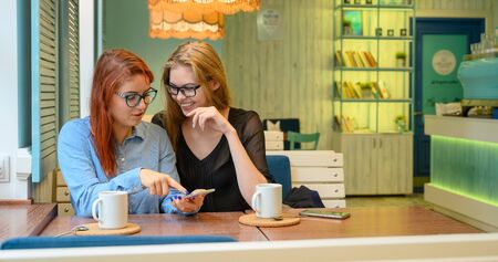 Two excited young girls using mobile phones, sitting in a cafe and pointing finger. Red-haired woman in glasses shows her friend funny photos on a smartphone girlfriend blonde. They drink coffee. Stock Photo