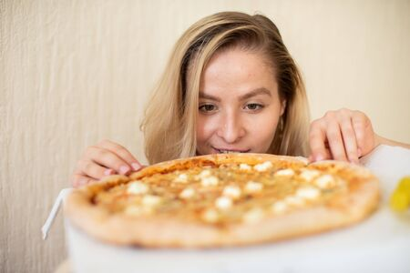 Portrait of a woman eating pizza. Beautiful young woman in black underwear eating pizza
