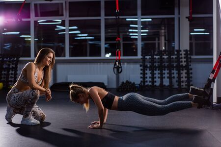 Female fitness instructor conducts personal training. Young attractive woman push ups with TPX loops on her legs. The girl is engaged with a trainer, makes the bar with straps TPX.