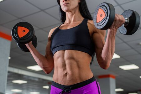 A powerful, strong, muscular girl with beautiful abdominal muscles holds dumbbells in her hands. Daylight ABC