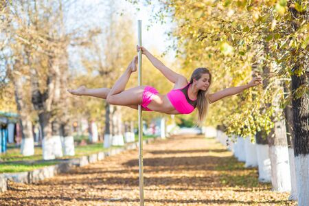 beautiful gymnast do tricks on a portable platform in a beautiful autumn park. woman dance on a portable pole stage against the backdrop of autumn leaf fall. Pole dance. A stunning dance.