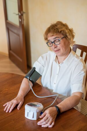 An elderly woman with glasses measures blood pressure using an electrical device in a bright room. Retired woman in a white blouse uses a tonometer at home sitting at the table