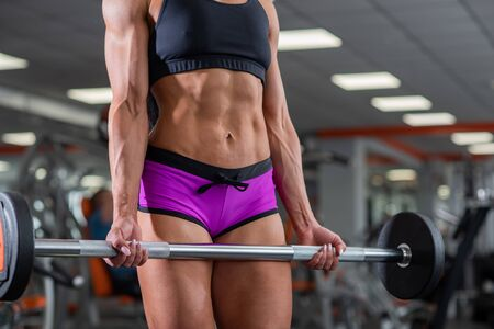 A powerful, strong, muscular girl with beautiful abdominal muscles holds barbell in her hands. Beautiful woman in the gym shakes triceps. Bodybuilder is preparing for the competition. Close-up Фото со стока